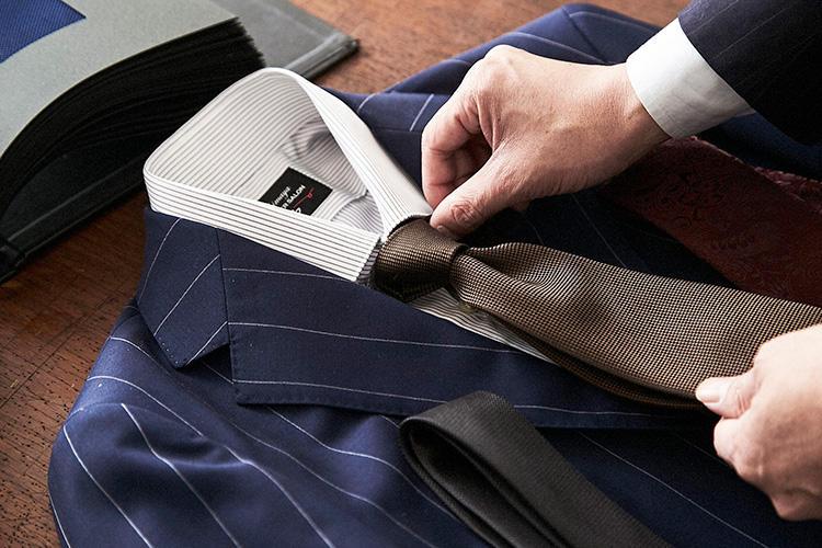 <strong>「合わせやすいネクタイの色はどれだろう」</strong><br />イタリア男が好むカラーコーディネート「アズーロ・エ・マローネ(紺×茶)」を意識して、ネイビースーツにはブラウンタイを。スーツが柄入りなので、無地にして織り感のある生地を選んだ。