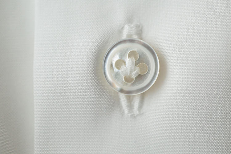 """<strong>ボタンは""""本""""白蝶貝!</strong><br />ミシンで鳥かけ風に留めたボタンも、イタリアシャツ風。ボタンの素材も本物の白蝶貝を使っているため、白くて美しい。"""