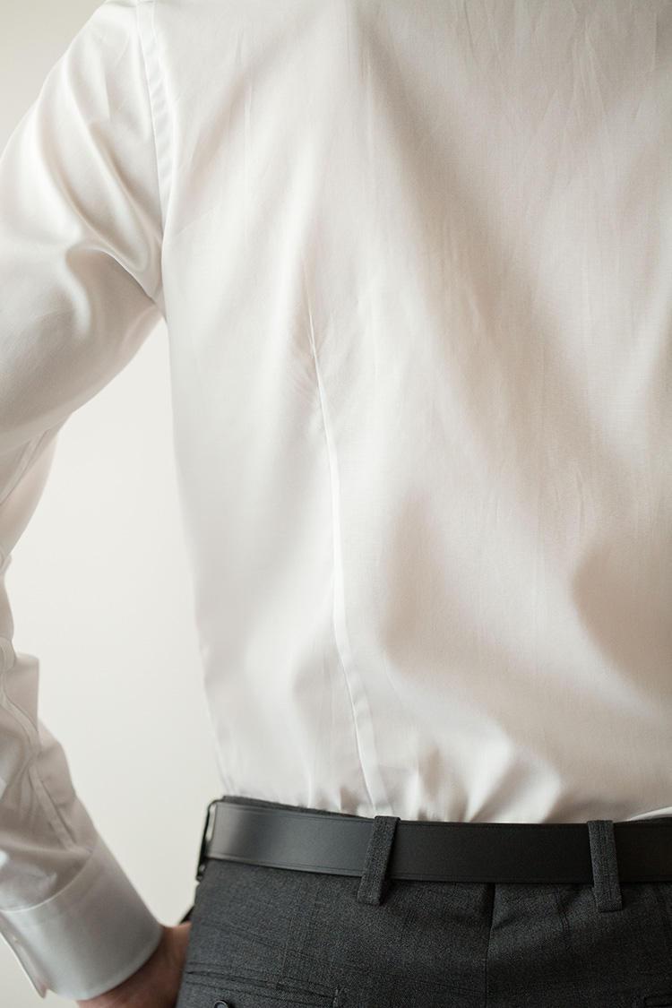 <strong>背中を美しく魅せるバックダーツ後ろ姿をスッキリ見せる</strong><br />バックサイドダーツを執ることで、身幅を絞ってスリムに見せることでシワやダブつきの少ない美しいシャツを実現。シャツ一枚のときでも後ろ姿を美しく見せてくれる効果もある。