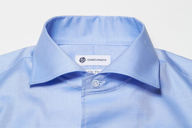 <strong>【セミワイドカラー】</strong><br />クラシックなドレスシャツの定番襟型。カミチャニスタのセミワイドカラーは襟開き角度が大きくフォーマル&ドレッシーな印象が漂う。タイドアップしたときも襟元が男らしく決まるのだ。