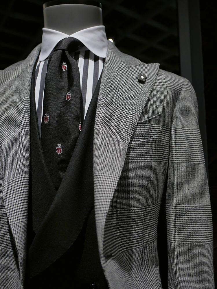 <b>ラルディーニ</b></br>グレーのグレンチェックとグレーのロンストクレリックシャツ。どちらも強めの柄ながら、間に黒のベストを挟み、黒のクレストタイでシャープにまとめたことでシックなモノトーンの胸元に。派手めのロンストシャツは、このように間にベストを挟むとシャツの見える面積も少なくなり、柄の強さを中和できる。
