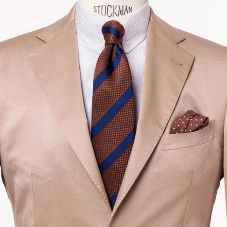 <strong>9. 上級編・茶の同系色</strong><br />スーツほどカタすぎず、ジャケパンほどユルすぎない立ち位置が魅力のコットンスーツ。<br />定番のベージュを選んで、赤茶のストライプネクタイと同系色でまとめれば、タダ者ではない着こなしに。