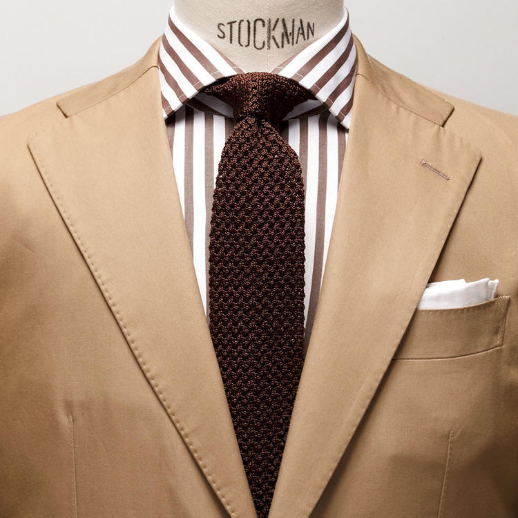 <strong>10. 上級編・いつかはソラーロ</strong><br />茶の同系色でまとめるなら、イタリアでポピュラーなソラーロ生地のスーツもおすすめ。<br />玉虫色のほのかな光沢が何ともお洒落なこのスーツは、焦げ茶のニットタイとリラックスムードで着こなすのが王道だ。