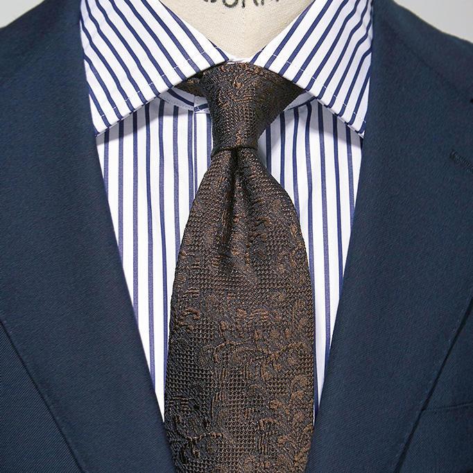 <strong>4.反対に幅広ストライプになると?</strong><br />間隔が空いた紺ストライプは白場が多い分、印象が爽やか。コーディネートは1.5柄の法則に基づき、はっきりしたストライプのシャツを1柄、茶の織り柄ネクタイを0.5柄、紺無地スーツを0柄と数えて組み合わせた。紺×茶も覚えておきたい王道の色合わせだ。