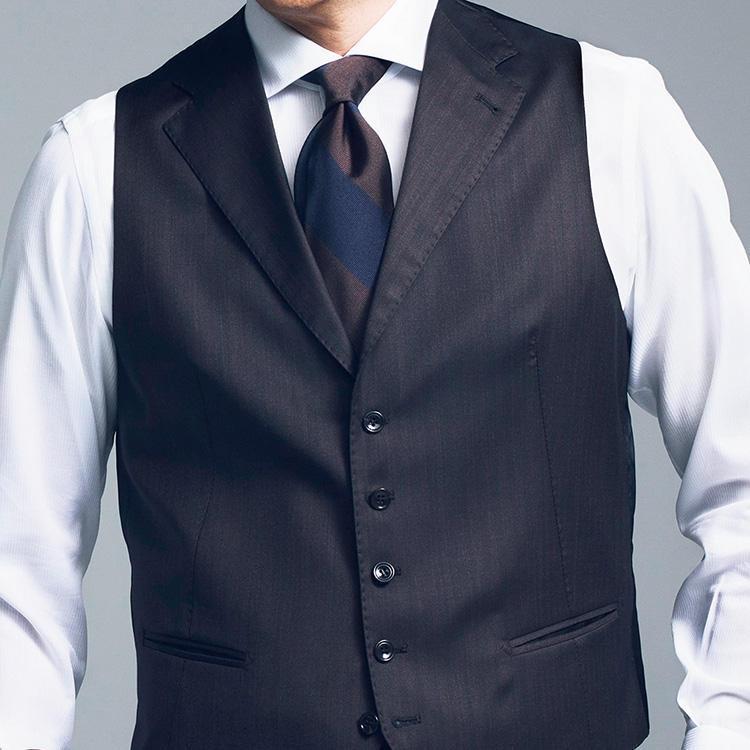<strong>3.焦げ茶ストライプの安定感</strong><br />定番のストライプネクタイも茶ベースだと新鮮。<br />紺×茶の配色ネクタイなら家にある紺系スーツに合わせやすい。<br />写真は茶系の3ピースの上着を脱いだ状態。<br />ベストは今トレンドの襟付きだ。