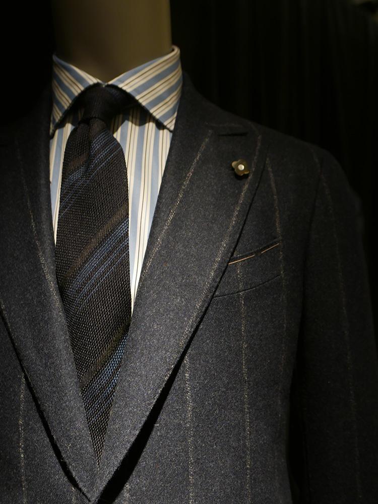 <b>ラルディーニ</b></br>かなり濃いめのグレーストライプスーツ。シャツもネクタイもストライプで計3柄を使いながら、スーツのペーンのブラウンがシャツ・ネクタイの柄に拾われているのでバランスが良い。ネクタイの色みがストライプながらダークトーンで渋くまとまっているのが全体を落ち着かせた勝因。