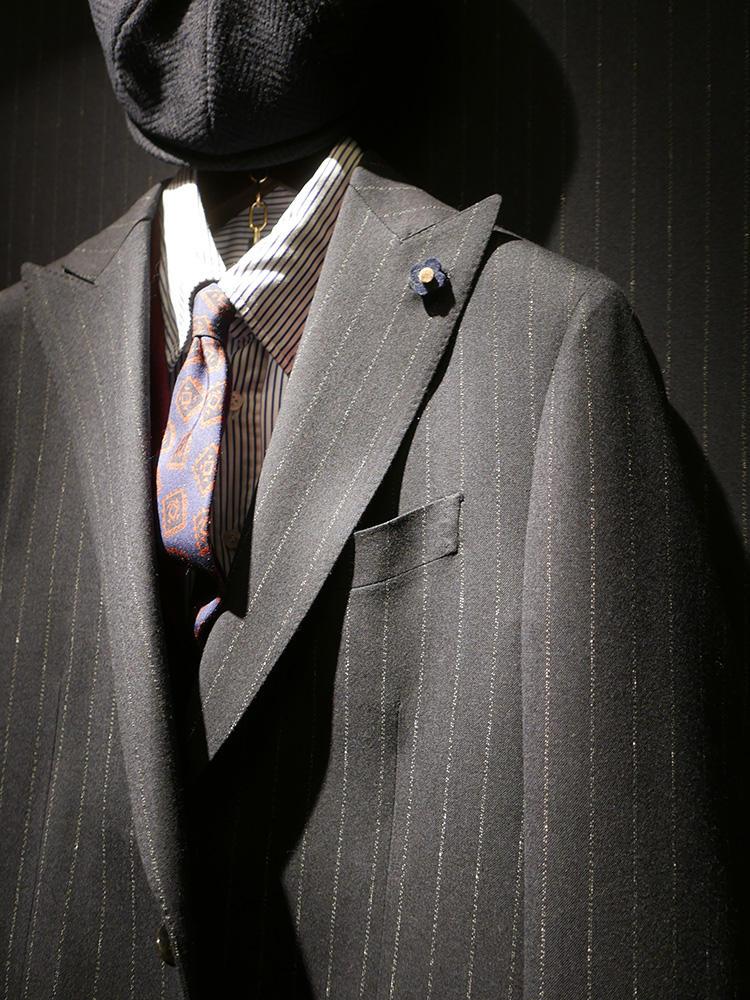 <b>ラルディーニ</b></br>こちらはミディアムグレーのストライプスーツに、ストライプシャツ。ストライプのピッチ幅をばらしているので、くどくならない。ネクタイは大柄のヴィンテージ調だが少し色褪せたトーンを合わせることで落ち着きをプラス。