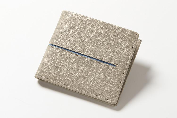 <strong>TOD'S/トッズ</strong><br />型押しカーフの2つ折り財布は、アクセントとしてコントラストカラーが覗くセンターラインがアイコンデザイン。極上に柔らかく、2つ折りのままでもさらに曲げられそうなほど。淡いトーンの発色が、優雅な趣を薫らせる。横11×縦9.5×マチ2.5cm。3万8000円(トッズ・ジャパン)