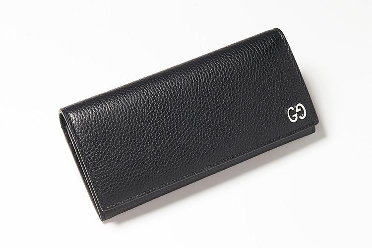 <strong>GUCCI/グッチ</strong><br />シボ革のロングウォレットは柔らかく手触りのよい質感。これまでジャカードや型押し、プリント柄などで見られた「GG」ロゴをメタルピースであしらいにさりげなく高級感とブランドの品種が漂う。背面にもチケットポケットが配されている。縦9.5×横19×マチ3cm。8万2000円(グッチ ジャパン)