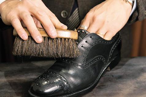 <strong>4.馬毛ブラシでホコリ取り</strong><br />毛足が長く隅々まで毛先が入り込む馬毛ブラシを使い、靴全体を優しくブラッシングしていく。