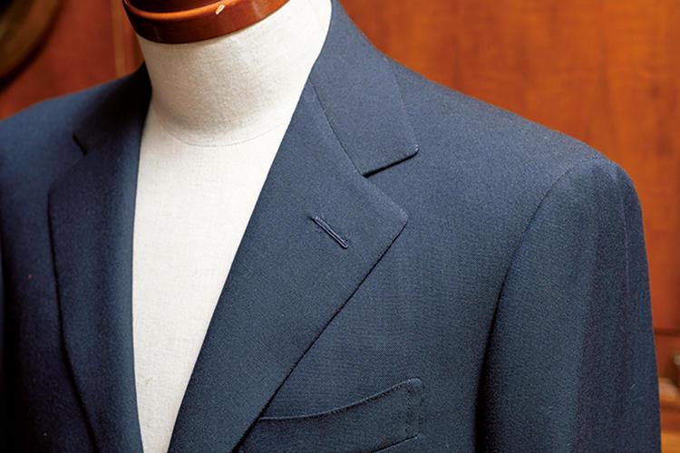 <strong>丁寧な縫製が生むクリーンな表情</strong><br>ゴージやラペルの端、やや大きめのフラワーホールに至るまで、非常に丁寧なステッチが施されている。手縫いを誇張しない縫製が上品だ。