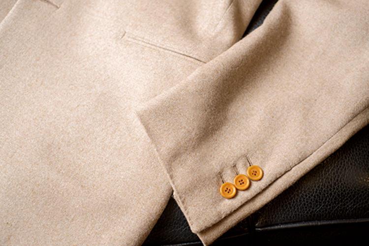 <strong>袖のボタンは3つがスタイル</strong><br>イタリアやイギリスのスーツは袖ボタン4つが一般的だが、山上氏は3つが定番。また身頃のポケットはフラップなしの両玉縁を基本としている。