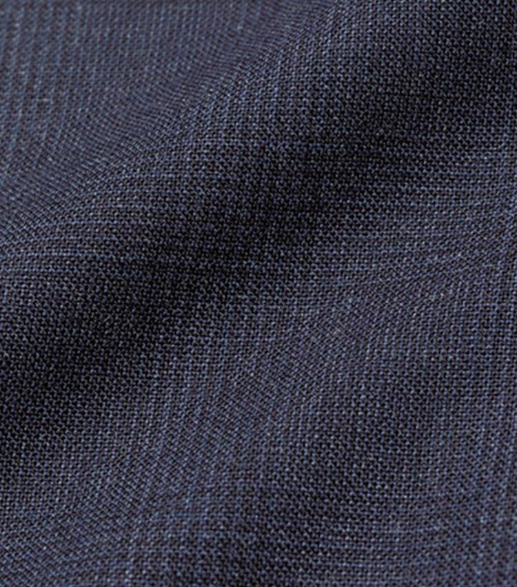 <font style=font-size:1.2em><strong>ウィリアム・ハルステッド生地</strong></font><br><br><strong>仕立て映えするハリコシの強い英国生地</strong><br>前ページのスーツの素材は、英国毛織物の聖地として知られるハダースフィールドの老舗「ウィリアム・ハルステッド」社製の強撚ウール地。英国生地の王道を行くハリコシを備えた、通好みの生地である。一方、コントラストを抑えたダークな柄行きには、モダンな趣も。