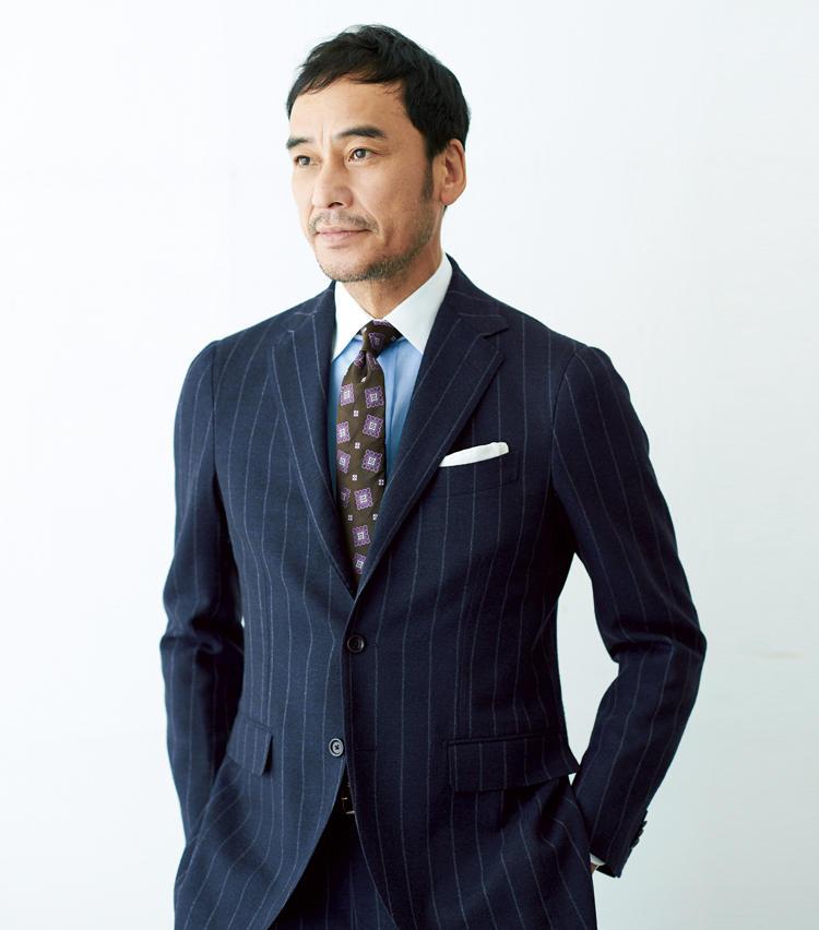 <span style=font-size:1.1em;><strong>パープル×ブラウンタイが格調と柔和さを演出</strong></span><br />「タイを定番のネイビーからパープル入りのものに替えるだけで、王道の紺ストライプスーツも新鮮に。こちらは地色がブラウンですが、実はパープルとブラウンはとても相性のいい色。柄色の紫を引き立てつつ、装い全体を柔和な印象に見せる効果もあります。シャツはコントラストの強い白よりブルー系が相性よし。普通の青無地でもいいのですが、旬のブリティッシュを意識して、ここではクレリックをセレクトしています」。<br /><span style='font-size:0.8em;'>タイは上写真のルイジ ボレッリと同じ。スーツ11万円、シャツ1万4000円、チーフ2800円/以上ビームスF(ビームスF)</span>