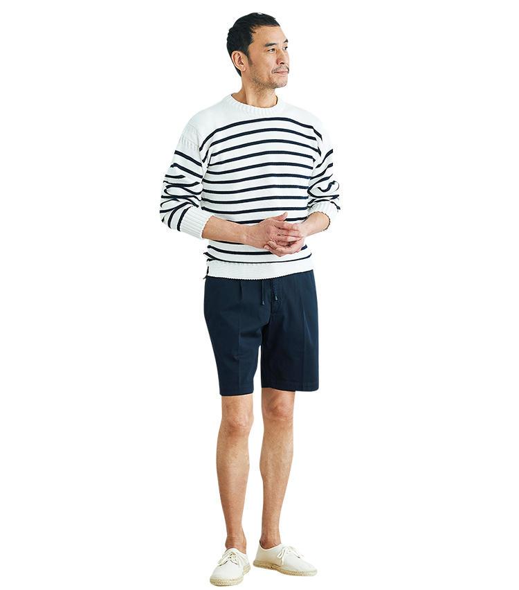 <span style='font-size:1.1em;'><strong>【着こなし3】ボーダー×ショーツを大人に見せるコツ</strong></span><br />「ショートパンツにボーダーニットのスタイルは涼しげで爽やかですが、子どもっぽく見えないよう配慮が必要。そこで、長袖のニットを袖まくりして大人な印象に見せています。ネイビー&ホワイトの2色に色数を絞っているのも上品に見せるポイントですね。足元は上と同じジュートソールですが、こちらは白スニーカー風のアッパー。靴を明るい色にしているぶん、さらに軽やかな印象になります」。<br><span style='font-size:0.8em;'>ニットは前ページのガンジー ウーレンズと同じ。ショーツ2万3000円/ジャブス アルキヴィオ、靴9000円/ライス(以上ビームス 六本木ヒルズ)</span>