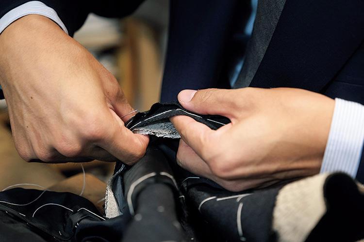 袖のしつけをしている工程。イセ込み量を左手の形で加減しながら、感覚的にしつけていくのが特徴。