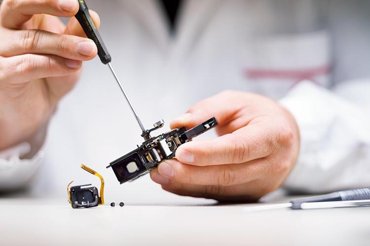 写真はローラーレバーをレンジファインダーに取り付けているところで、熟練職人の繊細な技術を必要とする。