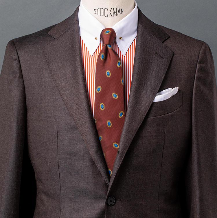<b>1.暖色でまとめた装いの中でクレリックの白襟がヌケ場に</b><br />微光沢をたたえたブラウンスーツ自体が秋を意識させるのに、シャツ+タイも暖色としたことで、より季節に相応しいムードとウォーム感を得ている。それでいて端正さも感じさせるのはクレリックシャツの白襟がヌケ場となっているため。その襟のピンホールにゴールドのカラーピンを挿したことで、秋色でまとめたスタイルが一層格調高く見えるのもいい。