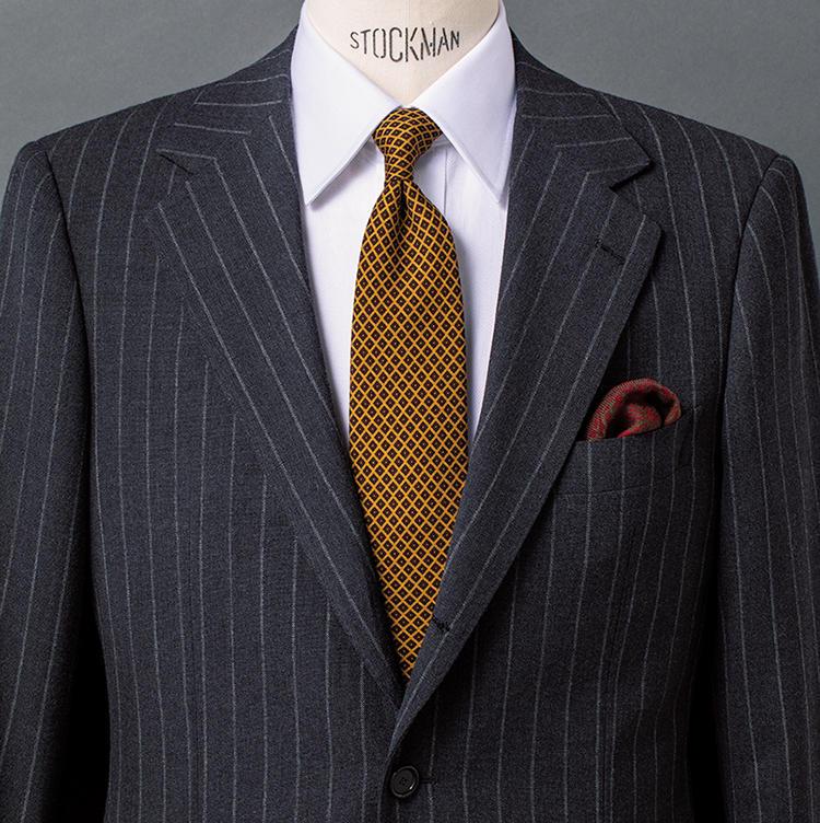 <b>2.イエローとボルドーを効かせグレーチョークを華やかに</b><br />明るいイエローベースに細かな幾何学小紋を配したタイと、胸元のボルドーベースのチーフで秋らしいエレガンスをプラス。グレーのチョークストライプスーツが打ち込みのしっかりした生地ということもあり、英国テイストの色気も濃厚に感じさせる。地位や年齢に相応しい貫禄を保ちつつ、さりげなく攻めてみたいという人におすすめの組み合わせだ。