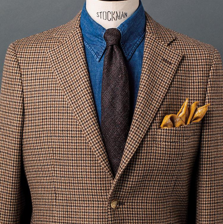 <b>3.カントリーな秋色表現を青シャンブレーが馴染ませる</b><br />ヘリテージ柄のトレンドに沿うガンクラブチェックのジャケット。そこに青シャンブレー生地のタブカラーシャツと茶ベースのメランジタイを合わせ、スポーティさとドレスな品とが絶妙にバランスしたスタイルを築いた。このシャツの生地感と色合いのおかげで、ジャケット、タイ、チーフの3点で暖色を取り入れたコーデも絶妙に馴染んでくれるのだ。