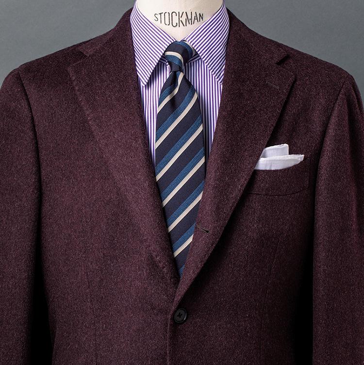 <b>4.ノーブルさが際立つパープル×パープルの合わせ</b><br />ジャケットは名門ロロ・ピアーナ社のカシミア100%生地を使用。上品なダークパープルといい、程よく起毛した風合いといい、秋らしい色気演出には絶好の一着だ。ここではシャツのストライプも淡いパープルとしたことで、一層ノーブルな雰囲気に。甘くなりすぎないよう、ネイビー×ブルー×白のシャープなストライプタイで締めたのもコツだ。