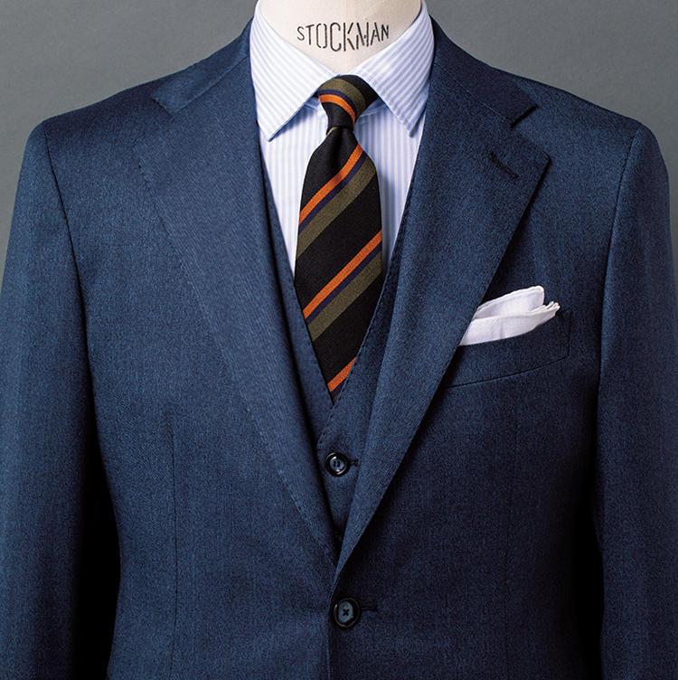 <b>7.ネイビースーツを今に見せる黒レジメンタイ</b><br />正統派のネイビー3ピースに、やや挑戦的な黒タイという落差のある組み合わせ。今らしさを演出したいときに好適だ。とはいえご覧のタイは、グリーンとオレンジとの3色ストライプとなっており、トラッドなテイストも強い。ゆえに正統派のネイビースーツを一層キリッと見せるうえでも役立つ。素材がウール混である点も、これからの季節に向く。