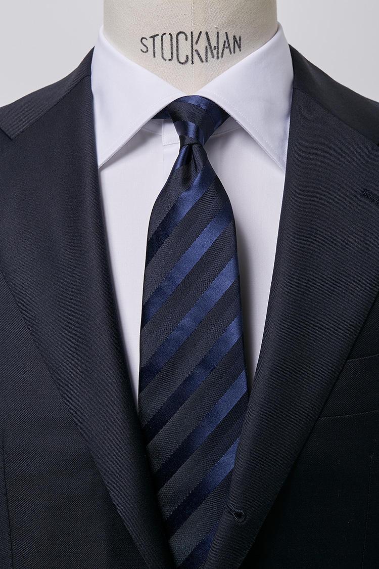 <b>【艶気】<br />ホワイトのブロードセミワイドカラーシャツ × かすみ織りレジメンタルタイ</b><br />ブロード織りの光沢に浮き上がる上品なかすみ織りの光沢が、艶感あるドレッシーなコーディネート。フォーマルな席にもふさわしいVゾーン。ブロードセミワイドホワイトシャツ5000円、かすみ織タイ6500円