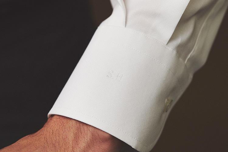 <strong>イニシャル刺繍は同色の糸でさりげなく</strong><br />白シャツに白糸でイニシャルを刺繍。袖口にあしらったのにも理由が。「ジャケットの袖をぐっと手繰ってお気に入りの時計を見るとき、シャツ袖にイニシャルがあると、オーダーシャツを着ている満足感が高まります」。