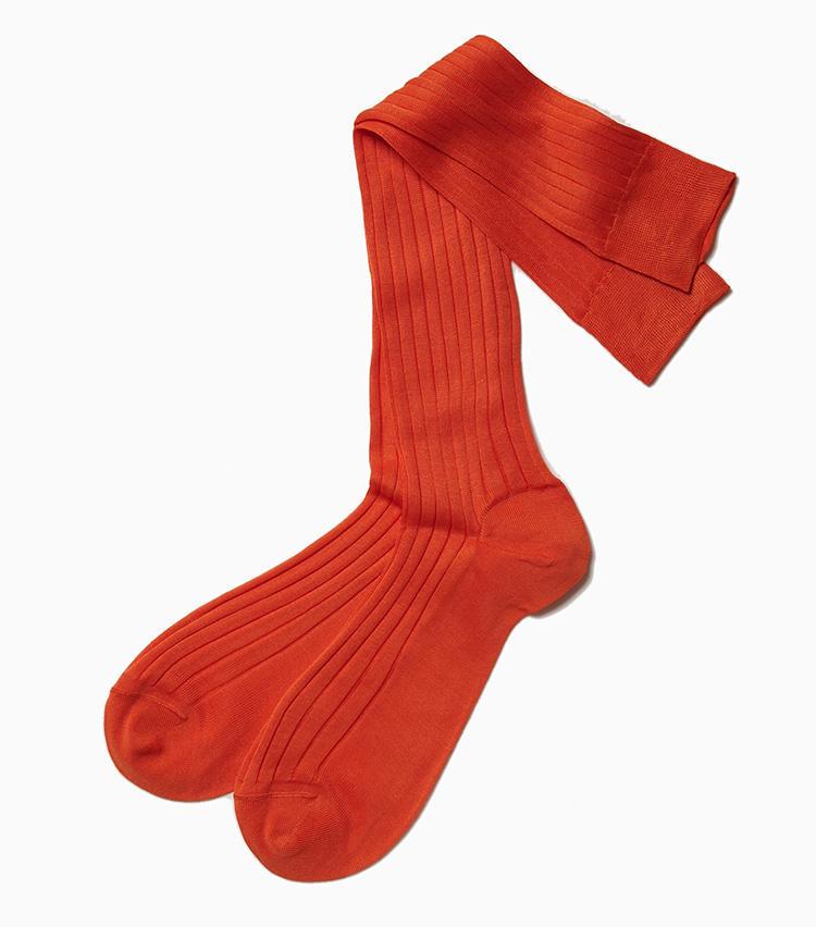 <b>18.アルトのオレンジホーズ</b><br />ビビッドなカラーホーズはラ ガゼッタ1987のアイコン的アイテムのひとつで、常に豊富な色バリエを揃えている。ミラノのソックスブランドによるこちらはドレッシーな薄手のリブ編みで、カジュアルなカラーソックスとは一味違った大人らしさが魅力。2300円(ラ ガゼッタ 1987 青山店