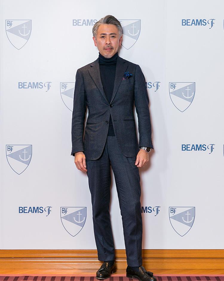 <strong>スーパーバイザー・津田 敬</strong>さん<br />グレイッシュなネイビースーツにタートルネックニットといういたってシンプルな合わせだが、完璧なサイズ感で非常に洗練された装いに。控えめに効かせた柄チーフも◎。