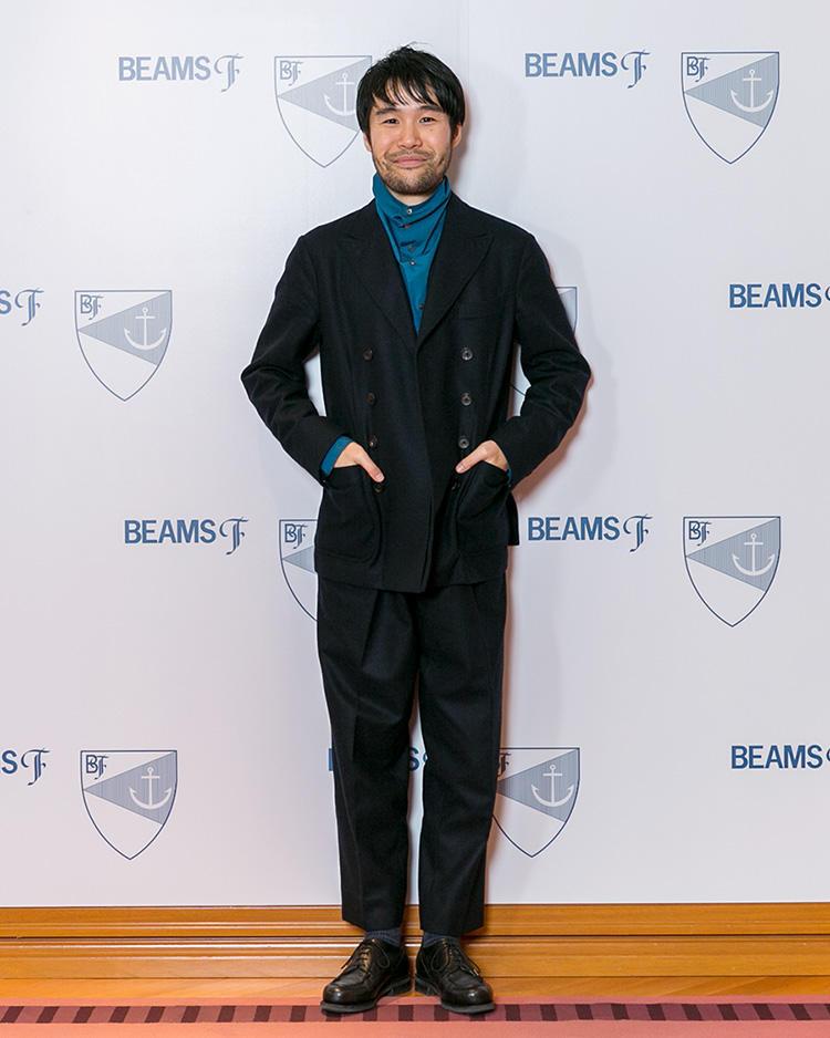 <strong>プレス・安武俊宏</strong>さん<br />8ボタンのダブルブレストスーツに合わせたのは、襟がボタン留めのハイネックになったバグッタのシャツ。シンプルだが印象的なアイテム選び&合わせにセンスを感じる着こなしだ。
