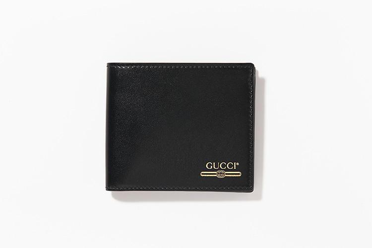 <strong>GUCCI</strong><br />ブラックのスムースレザーにあしらわれるゴールドの箔押しロゴは、'80年代のヴィンテージプリントにインスピレーションを得たもの。縦9cm×横11cm。5万5000円/グッチ(グッチ ジャパン)
