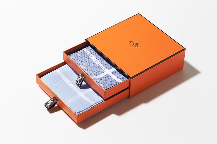 <strong>HERMÈS</strong><br />エルメスオレンジのボックスに、ハンカチーフを収納。「なんといっても、このオレンジの箱に入っているとギフトの格が上がります! きれいにアイロンが掛かった清潔感あるハンカチは、ビジネスマンの重要アイテム。引き出し式のボックスは折り目がぴったりせず、ふんわりさせたまま1枚ずつ仕舞えるのもいいですね」(ヒラサワ)。3万3000円/エルメス(エルメスジャポン)