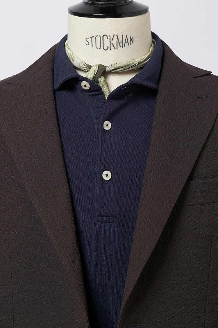 ジャケット+ニットポロのときは、フロントのボタンがある分、スカーフがあまりウルサクなりすぎないほうが◎。ねじりながらキュッとタイトな結び目で、先は中にIN。<br />スカーフ各7800円/アルテア、スーツ16万8000円/ザ・ジジ、ポロシャツ1万6000円/アルテア(以上アマン)