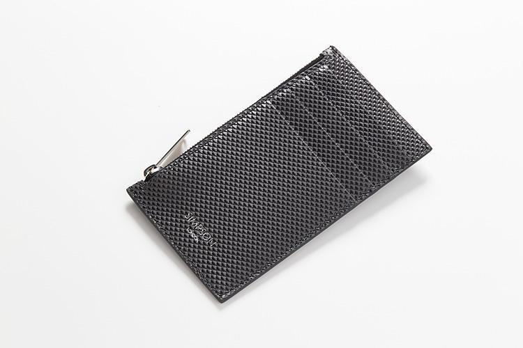 <strong>シンプソン ロンドン</strong><br />英国製のジップ付きカードケースは、凹凸のあるカーボンレザー製のため、暗がりでも手探りで取り出しやすい。カードスロット4室は外側にあり、改札やレジでそのままタッチもOKだ。縦13×横7.5cm。1万7000円(MIYAKE)