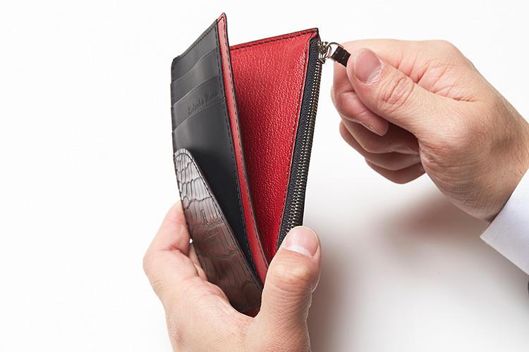 (同・ジップを摘んでいるところ)<br />カード、紙幣、小銭の専用ポケット付き。