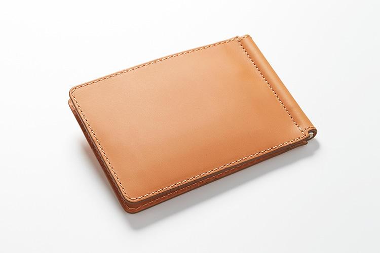 <strong>ジャン・ルソー</strong><br />時計ベルトのブランドとして名高いフランスの名門ジャン・ルソー。外側に使われているきめ細かいベビーカーフは、色名を「ゴールド」というだけ合って、金運の上がりそうなカラーである。縦8.5×横11.5×マチ1.5cm。3万1000円(アトリエ ジャン・ルソー)