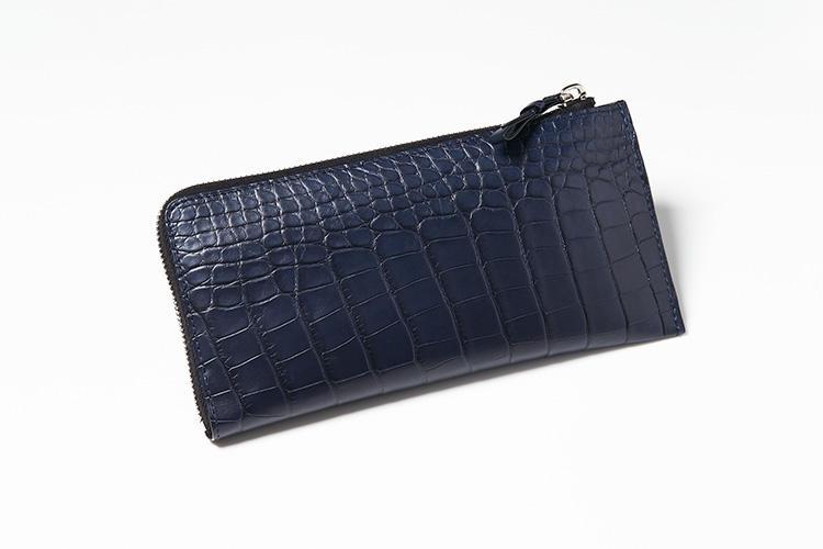 <strong>ジャン・ルソー</strong><br />L字のジップで開閉するウォレットは、本物のアリゲーターの革を贅沢に使用。深いネイビーカラーで落ち着きの中にラグジュアリー感を秘めた大人の風合いだ。片マチがないぶん薄手なので、上着の内ポケットに入れても収まりが良い。縦10×横20.5cm。18万円(アトリエ ジャン・ルソー)