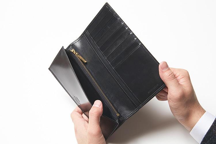(同・開いたところ)<br />フラップを上げると、目を引くのがブランドロゴの刻印。札室と平行してジップポケットを備え、フラップ裏にはカードポケットを8箇所、マルチポケット2箇所を用意している。