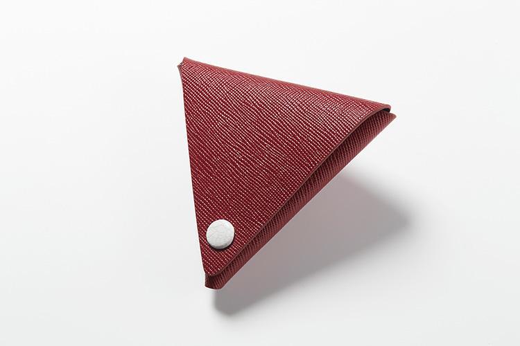 <strong>メゾンタクヤ</strong><br />1枚の革を折り紙のように折りたたんだ三角形の「Vコインケース」。表にはイタリア産のサフィアーノレザー、内側にはAランクのフレンチゴートを採用して、糸で縫い合わせるのではなく張り合わせたつくりにも高い技術力が感じられる。縦8.5×横8.5×マチ1cm。1万4000円(ファーレ)