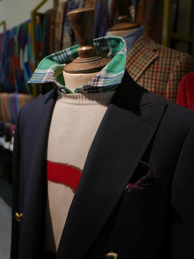 <b>ドレイクス</b></br>ネイビージャケットの下に、ロゴ入りニットとマドラスチェックシャツ。シャツの襟を立てるとリラックス感もUP。