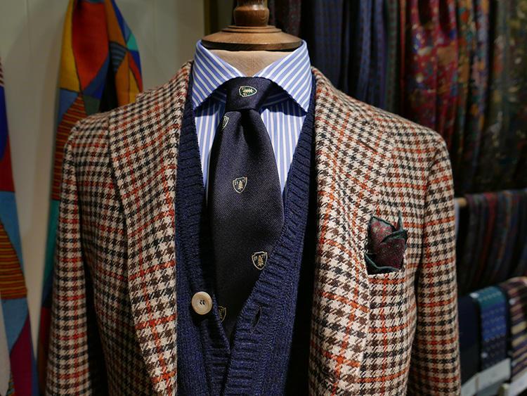 <b>ドレイクス</b></br>かなりカラフルなガンクラブチェックのジャケット。ロンストシャツにネイビーのクレストタイ、いずれも柄モノ合わせだが、間にネイビーのベストを挟んだことでシックな印象が加わった。