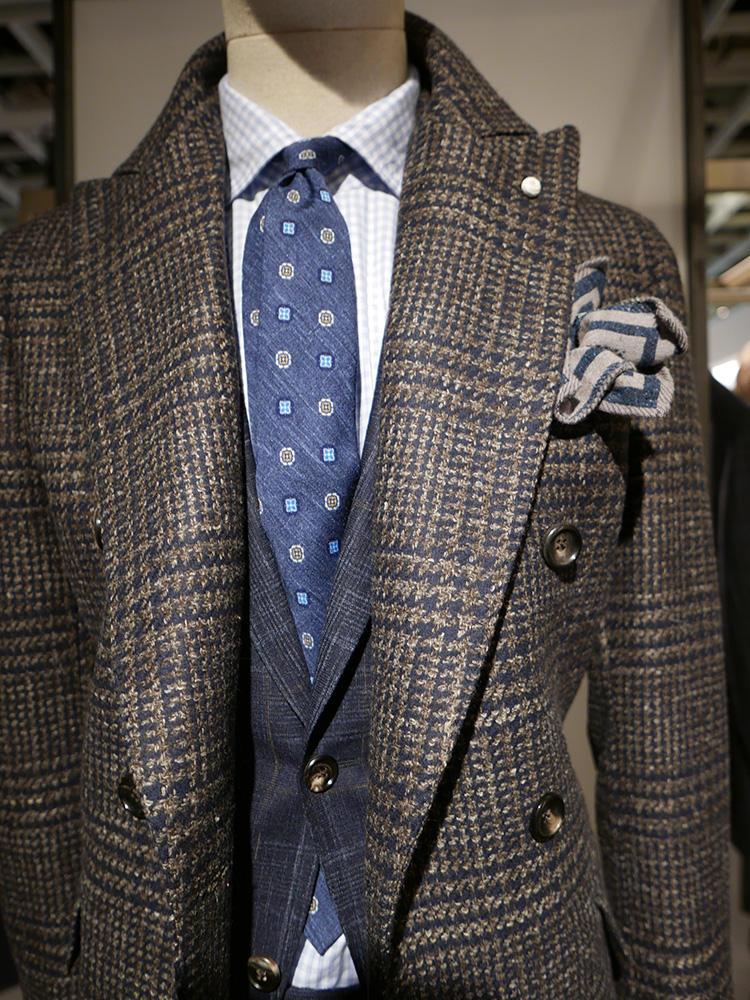 <b>ルイジ ビアンキ マントバ</b></br>こちらは前の写真と逆で、コートがブラウン系、スーツがネイビー系を合わせた例。全体を紺×茶系の色に絞ると、柄モノでも簡単に美しく配色をまとめることが出来る。