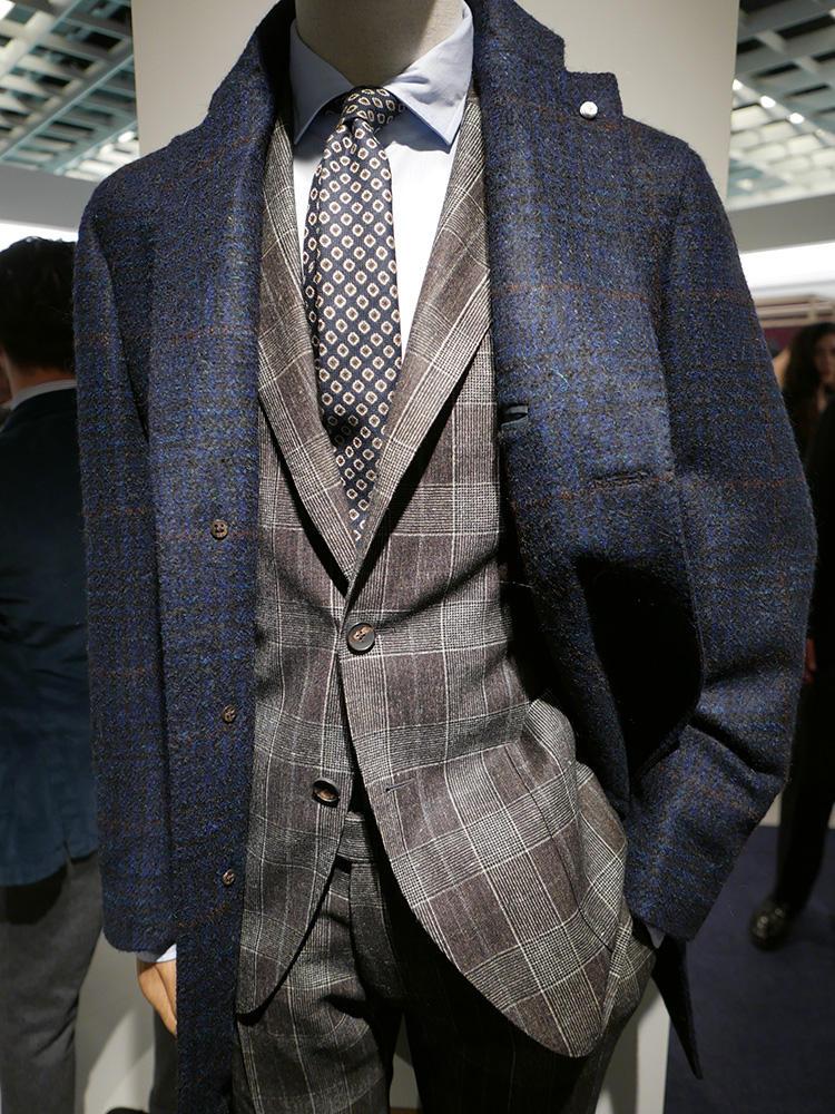 <b>ルイジ ビアンキ マントバ</b></br>ブラウンジャケットの柄が強めのときは、このようにネイビーのコートを上に羽織ると、「アズーロ エ マローネ」効果で上品なまとまりに。ネクタイの小紋柄も、この鉄板配色を取り入れればさらにバランスがよくなる。