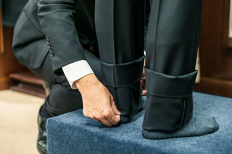 <strong>裾丈の基本は床から1.5cmほど</strong><br />まずは基準値となる長さで裾を折り返し、顧客の好みを聞きながらバランスを調整していく。