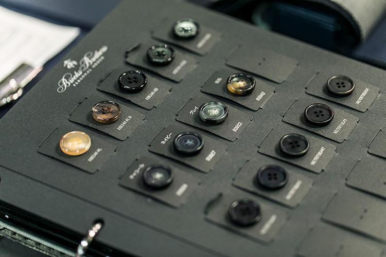 <strong>ボタンは約30種類から選べる</strong><br />ホーンボタン、ナットボタン、練りボタン、金属ボタンなど、約30種類あるボタンの中から、生地の表情やスタイルにマッチするボタンをセレクトします。