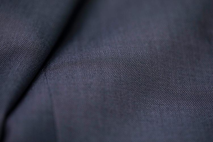 <strong>上品でいて洒脱なニュアンスも備えた生地</strong><br />ごく細かな織り模様が浮かぶ、ネイビーブルーの梳毛生地。艶もあり、上品でいながら適度なニュアンスを備える。目付は260gと中庸だ。