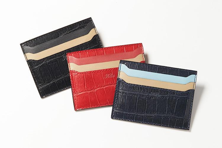 <strong>フェリージ</strong><br />両面収納できるカードケースは、極薄マチながら凹んだポケットのおかげで取り出しやすい。クロコダイルの型押しを施した外装と、品の良いグラデーションカラーになったポケットは、相手に好印象を残しやすいだろう。縦8×横10cm。各2万3000円(フェリージ 青山店)