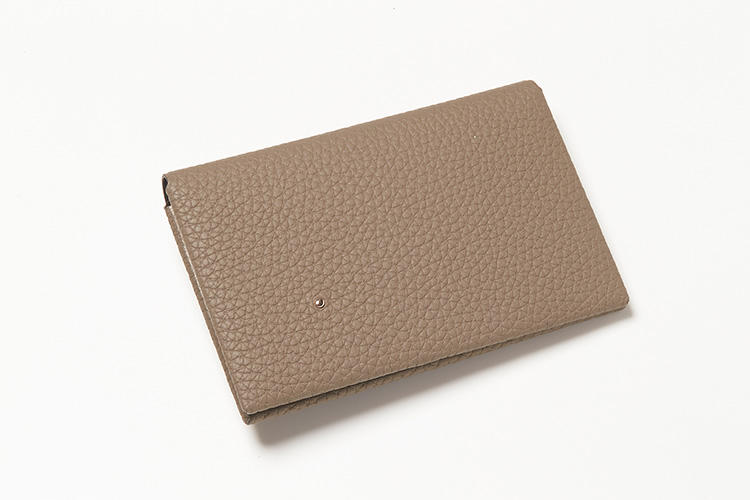 """<strong>4位 T・MBH</strong><br />こちらのティーエムビーエイチは、革小物司・岡本拓也氏のデザインと仕立ての指示のもと、浅草橋の工房にて製作しているオールハンドメイドのブランド。まるでえくぼのような18金ピンクゴールドのアクセントには、女性の視線が集中しそう。「""""葉合わせ""""という縫わずに仕立てるオリジナル製法を採用。封筒型のため、一見コンパクトでも、なんと何十枚も収納可能な大容量。写真の名刺入れは外装がシュランケンカーフ。外装はほかにもワニ革やトカゲ革、象革など、バリエーション豊富に選べるところも人気です」縦6.8×横10cm。2万7000円(伊勢丹新宿店)"""