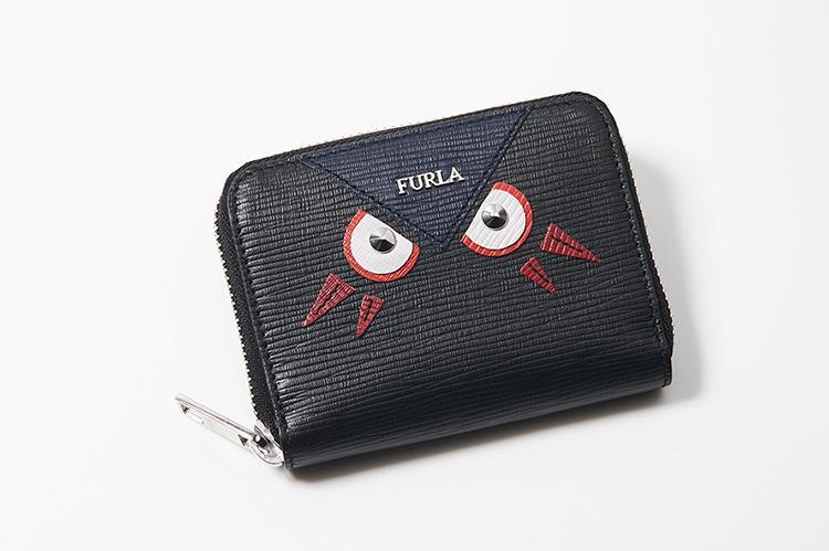 <strong>FURLA/フルラ</strong><br />サフィアーノ調の型押しレザーのカードケース。背面にカードポケット付き。スタッズの目をもつユニークなフルラのキャラクターは、三角の額にブランドロゴがあしらわれている。この額、じつはハートマークの一部で上半分のキャラクターも同じシリーズに存在する。パートナーと二人で持ってはいかが。縦7.5×横10.5cm。2万5000円(フルラ ジャパン)